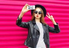 Gör den nätta kvinnan för mode självståenden på smartphonen i svart att vagga stil över stadsrosa färger arkivbilder
