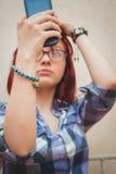 Gör den nätta unga flickan för mode selfieståenden på smartphonen royaltyfria bilder