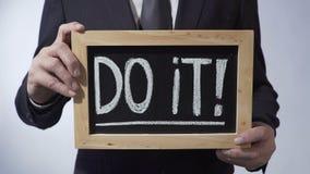 Gör det med den skriftliga utropsteckenet på svart tavla, det manliga hållande tecknet, motivation stock video
