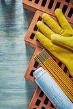 Gör en skiss av metern för röda tegelstenar för skyddande handskar träpå den wood boaen royaltyfri foto