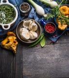 Gör grön plocka svamp säsongsbetonade matlagningingredienser för höst med skördgrönsaker, och på mörk lantlig träbakgrund Arkivbild