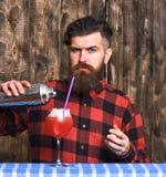 Gör hällande exponeringsglas för bartendern eller för hipsteren, den nya drinken med is Arkivfoto