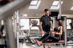 Gör iklädd svart sportkläder för härlig slank flicka övningar för abdominalsna på en special övningsmaskin royaltyfri bild