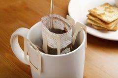 Gör kaffe vid droppande att brygga med kakan Arkivfoton