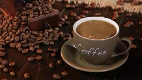 Gör latte i den lilla koppen som är fyllt svart kaffe arkivfilmer