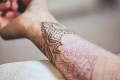Gör ledar- skyddande handskar för tatuering en tatuering i svart färgpulver på handen Royaltyfri Fotografi