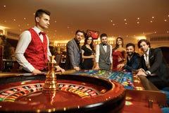 Gör lyckliga vänner för grupp vad som gambiling på rouletttabellen i kasinot arkivbild