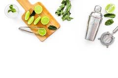 Gör mojitococtailen med limefrukt och mintkaramellen Shaker filter, glass near skivor av limefrukt på skärbräda på vit royaltyfria foton