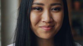Gör perfekt den slowmotion ståenden för närbilden av den charmiga asiatiska flickan med mörka ögon, hud med smink- och vittänder  lager videofilmer