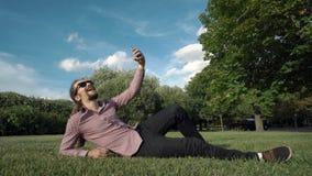 Gör selfie i ett offentligt att parkera: ila telefonen, foto arkivfilmer