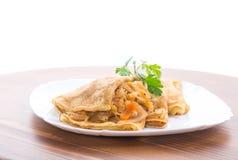 Gör stekte pannkakor som tunnare är välfyllda med kokt kål i en platta Royaltyfri Foto
