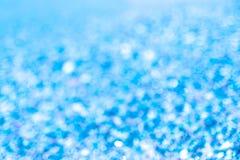 Gör suddig abstrakt blå bakgrund som blinkar ljusbokeh fotografering för bildbyråer