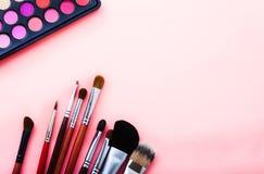 gör upp hjälpmedel Ögonskugga, borstar Skönhetsmedel på rosa bakgrund Top beskådar Åtlöje upp kopiera avstånd gör upp produkter Arkivfoto
