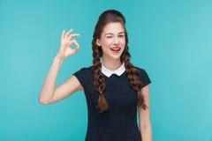 Göra en gest det toothy leendet för kvinnan och uppvisning av det ok tecknet på kameran arkivbild