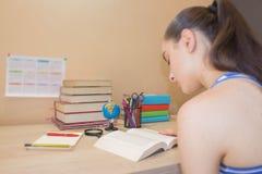 göra flickan henne läxa Skolböcker på skrivbordet, utbildningsbegrepp Ung flicka som hemma gör kurser Royaltyfria Foton