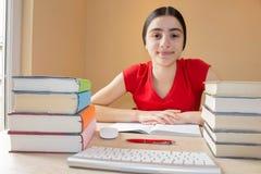 göra flickan henne läxa Skolböcker på skrivbordet, utbildningsbegrepp Ung flicka som hemma gör kurser Fotografering för Bildbyråer