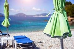 Göra grön det sunbed paraplyet på den vita stoestranden vid klart turkosblått vatten av medelhavet på solig varm sommardag arkivbild