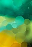Göra grön gula lutningoljadroppar i vattnet - abstrakt bakgrund Arkivbilder