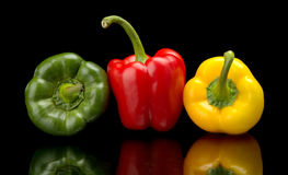 Göra grön, gulna spanska peppar som isoleras på svart, rött Royaltyfria Bilder