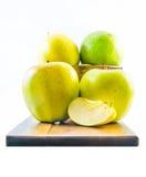 Göra grön och gulna äpplen med en skiva på ett träbräde på en vit bakgrund Arkivfoto