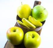 Göra grön och gulna äpplen och skivor i en violett kopp på ett träbräde på en vit bakgrund Arkivbild