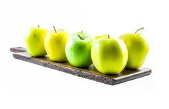 Göra grön och gulna äpplen på ett träbräde i en vit bakgrund Royaltyfria Bilder