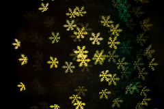 Göra grön och gulna snöflingabokeh i mörkret Royaltyfria Bilder