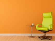 Göra grön stolen mot den orange väggen Arkivbild
