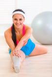 göra gymnastisk le sträckning för övningsflicka Arkivfoton