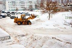 Göra klar insnöade Ryssland Väghyveln gör klar vägen efter ett tungt snöfall Traktoren gör klar vägen i borggården av envåning royaltyfria bilder