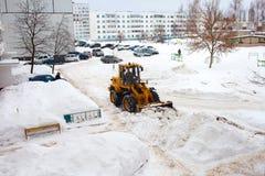 Göra klar insnöade Ryssland Väghyveln gör klar vägen efter ett tungt snöfall Traktoren gör klar vägen i borggården av envåning arkivfoto