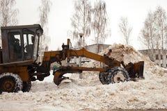 Göra klar insnöade Ryssland Väghyveln gör klar vägen efter ett tungt snöfall Traktoren gör klar vägen i borggården av envåning royaltyfria foton