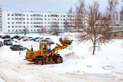 Göra klar insnöade Ryssland Väghyveln gör klar vägen efter ett tungt snöfall Traktoren gör klar vägen i borggården av envåning royaltyfri foto