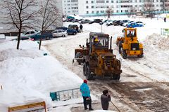 Göra klar insnöade Ryssland Väghyveln gör klar vägen efter ett tungt snöfall Traktoren gör klar vägen i borggården av envåning arkivbild