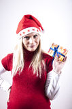 Göra panikslagen gravid kvinna med jul hatt och gåva Royaltyfri Fotografi
