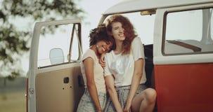 Göra perfekt att le, av två damer som spiriting på den retro bussen, och se rakt till kameran, ha ett lockigt hår 4K lager videofilmer