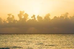 Göra perfekt den gula solnedgången på havet med pösiga moln Arkivbild