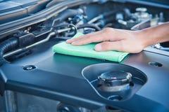 Göra ren bilmotorn med den gröna microfibertorkduken royaltyfria foton