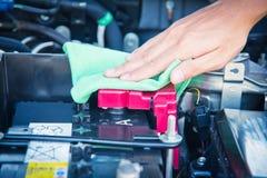 Göra ren bilmotorn med den gröna microfibertorkduken Arkivfoton