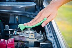 Göra ren bilmotorn med den gröna microfibertorkduken royaltyfri fotografi