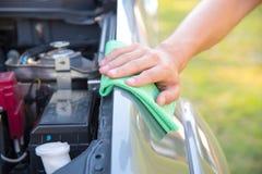 Göra ren bilmotorn med den gröna microfibertorkduken royaltyfri foto