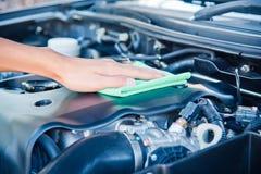 Göra ren bilmotorn med den gröna microfibertorkduken Royaltyfri Bild