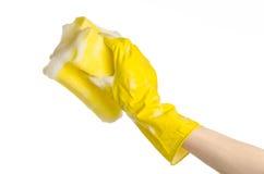 Göra ren hus- och sanitetsväsenämnet: Hand som rymmer en gul svamp våt med skum som isoleras på en vit bakgrund i studio Royaltyfri Fotografi