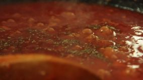 Göra sås och laga mat spagetti som är bolognese i köket arkivfilmer