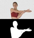 Göra sträcka den härliga unga kvinnan för övningar som gör sträcka övningar, medan gå, Alpha Channel arkivbild