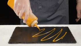 Göra till kok för restaurangmat Hällande dressing på plattan i ultrarapid Kocken i handskar häller sås på plattan Sunt stock video