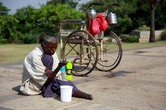 Göra till tiggare den rörelsehindrade kvinnan sitter för pengar från turister Med en rullstol på gatan, medan solen är varm Fotografering för Bildbyråer