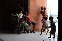 Göra till tiggare på rullstolen med andra tiggare och barn som har gyckel på den kyrkliga dörrportportalen Arkivfoton