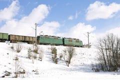 Güterzug, der durch Eisenbahnen im Winter überschreitet Lizenzfreie Stockbilder