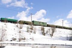 Güterzug, der durch Eisenbahnen im Winter sich bewegt Lizenzfreies Stockbild
